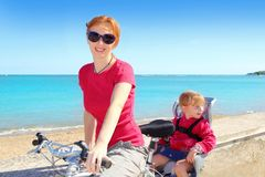 Daughter and mother on bicycle in beach sea Stock Photos
