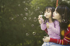 Daughter and mother blow soap bubbles Royalty Free Stock Image