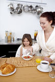 Daughter and mother in breakfast time Stock Image