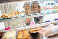 Daughter and mother choose sweets in candy store Royalty Free Stock Photography