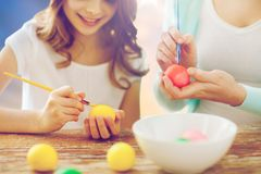Daughter and mother coloring easter eggs. Easter, family and holiday tradition concept - close up of happy little daughter and mother coloring eggs over sky Stock Photography
