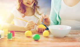 Daughter and mother coloring easter eggs. Easter, family and holiday tradition concept - close up of happy little daugter and mother coloring eggs over sky Royalty Free Stock Photos