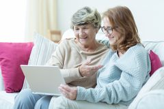 Daughter and mother with computer Stock Images