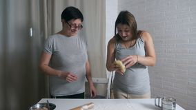Daughter and mother cook together in the kitchen, daughter helps mother knead dough for pancakes or cookies.  stock video