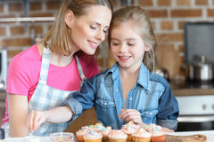 Daughter and mother decorating cupcakes with confetti Royalty Free Stock Image