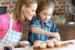 Daughter and mother decorating cupcakes with confetti Stock Image