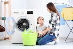 Daughter and mother doing laundry together. At home royalty free stock image