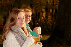 Daughter and mother drink tea in autumn park Stock Image