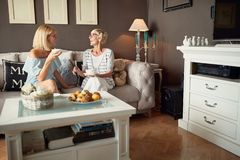 Daughter with mother drinking coffee. In room stock photo