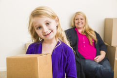 Daughter and Mother In Empty Room With Moving Boxes Royalty Free Stock Images