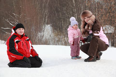 Daughter with mother, father sitting at snow Stock Images