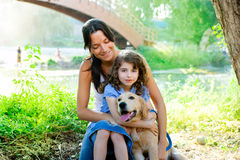 Daughter and mother with golden retriever Stock Image