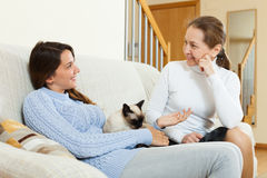 Daughter and mother gossiping on sofa. Smiling mother sitting on sofa with teen daughter and gossiping royalty free stock images