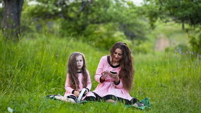 Daughter and mother headphones. Mom with her daughter and the white headphones on nature stock video