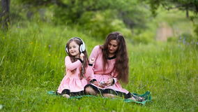 Daughter and mother headphones. Mom with her daughter and the white headphones on nature stock footage