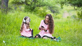 Daughter and mother headphones. Mom with her daughter and the white headphones on nature stock video footage