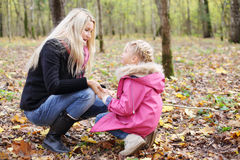 Daughter and mother hunker down and look at each other. Happy daughter and mother hunker down and look at each other in autumn forest. Focus on mother. Shallow stock image