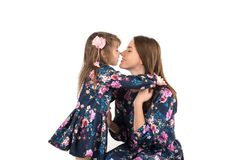 The daughter and mother in identical dresses look at each other Royalty Free Stock Photos