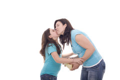 Daughter and mother kissing. A daughter kissing and giving her mother a present Stock Image
