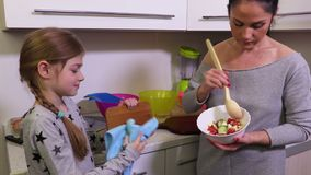 Daughter helps mother to cook stock footage