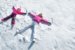 Daughter and mother laying on snow stock photos