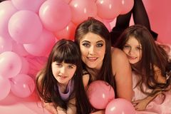 Daughter of the mother. Little girls, mom in pink balloons. Little girls with mom in pink birthday balloons in studio stock photo