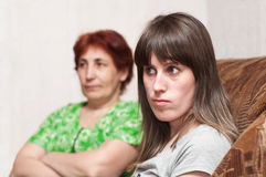 Daughter and mother are at loggerheads. Mature woman a mother and young girl a daughter together on sofa Royalty Free Stock Image