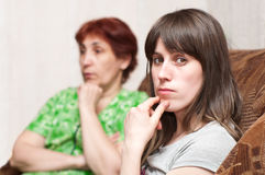 Daughter and mother are at loggerheads. Mature woman a mother and young girl a daughter together on sofa Stock Image
