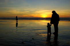 Daughter, mother and a lonely stranger. Daughter, holding her mother's hand, and a lonely stranger are watching sunset in San Francisco Stock Image