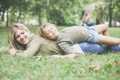 Little girl with her mother. Daughter and mother lying together on green grass. Playing in park royalty free stock photography