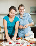Daughter with  mother making perogies with berries Royalty Free Stock Image