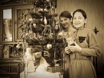 Daughter with mother near Christmas tree Royalty Free Stock Images