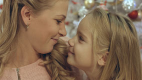Daughter with mother near the decorated Christmas tree Stock Photos