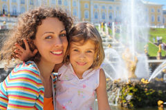 Daughter with mother near fountains of Petergof Stock Photos