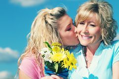 A daughter and mother on nice day. A daughter giving flowers to her mother on mother`s day Stock Photo