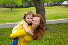 Daughter and mother piggyback smiling in park outdoor Royalty Free Stock Photo