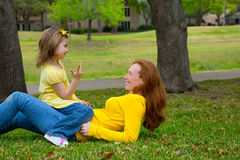 Daughter and mother playing counting lying on lawn Stock Photo