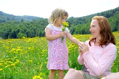 Daughter and mother playing in flowers meadow Stock Photo