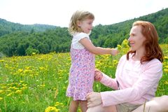Daughter and mother playing in flowers meadow Royalty Free Stock Photos