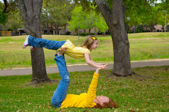 Daughter and mother playing keep balance lying on park Royalty Free Stock Photo