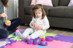 Daughter And Mother Playing Tea Party At Home. Cute little girl playing with toys wile sitting with mother on carpet at home stock image