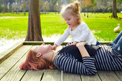 Daughter and mother playing together in park Royalty Free Stock Photos