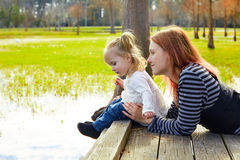 Daughter and mother playing together in park Royalty Free Stock Images
