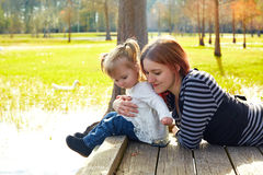 Daughter and mother playing together in park Royalty Free Stock Photo