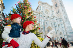 Daughter and mother pointing on something in Christmas Florence. Happy daughter and mother pointing on something while standing near Christmas tree and Duomo in stock image
