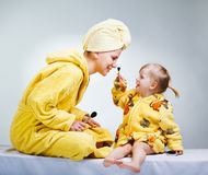 Daughter and mother putting makeup Royalty Free Stock Images