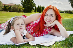 Daughter with mother resting on a green lawn. Royalty Free Stock Photo