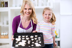 Daughter and mother showing their cookies Royalty Free Stock Images