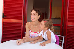 Daughter and mother sit on verandah round table. Near door and look aside stock photography
