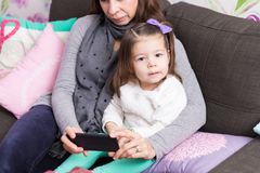 Daughter And Mother With Smartphone At Home. Portrait of cute girl sitting with mother using mobile phone in living room at home stock photo